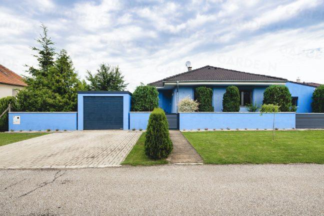 Modrá garáž zarovno plota