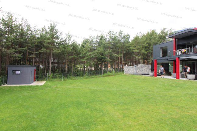 Záhradný domček v tmavo-sivej omietke pri modernom rodinnom dome