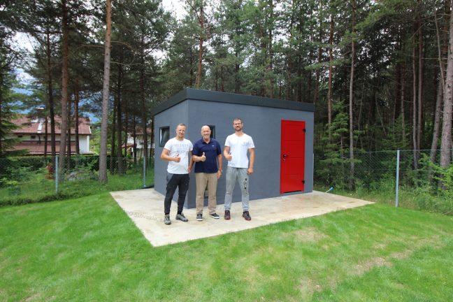 Spokojný zákazník pred záhradným domčekom v tmavo-sivej omietke s červenými dverami Hormann