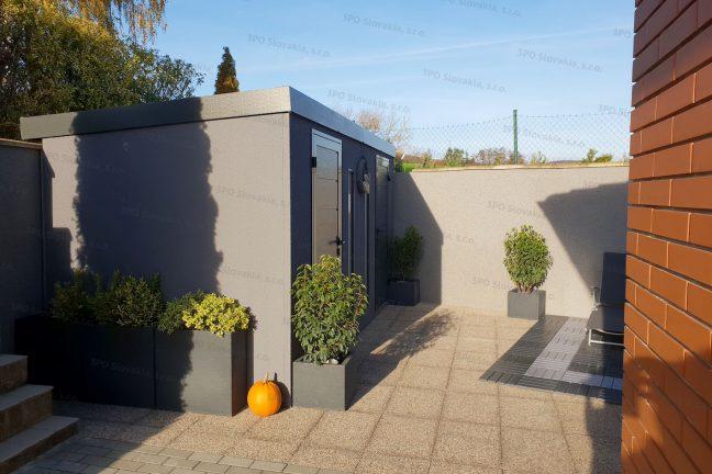 Záhradný domček na náradie v tmavosivej omietke pri rodinnom dome