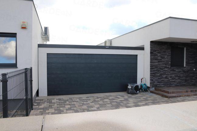 Dvojgaráž v bielej omietke s antracitovou garážovou bránou