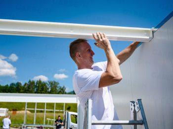 Montážnik ukotvuje biele nosníky na garáž